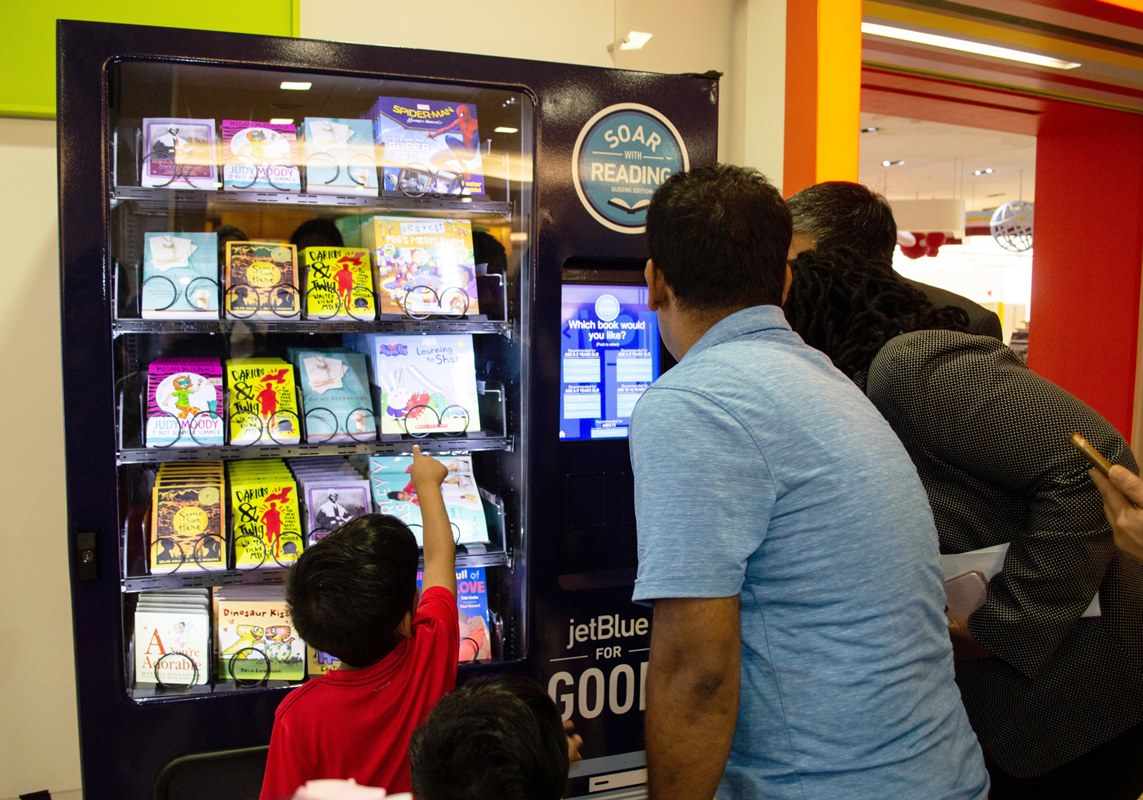 A child selects a book to take home from the JetBlue vending machine.